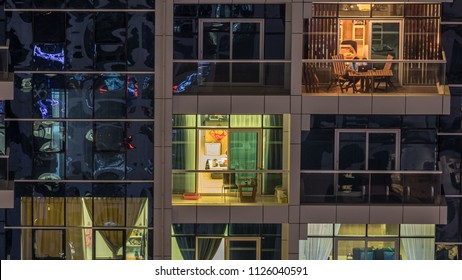Glowing windows of skyscrapers at evening timelapse. View of modern residential high-rise buildings in Dubai marina. People moving inside apartments. Aerial top view. Pan down