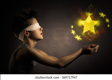 Glowing Yellow Stars Over the Open Hands of a Blind Boy with Bandage on his Eyes Against Gray Background.