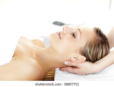 Glowing young woman  enjoying a massage in a spa center
