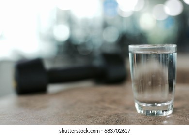 A glss of water with dumbbell in fitness gym