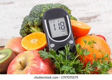 Glukometer zur Bestimmung des Zuckergehalts mit reifen natürlichen Früchten und Gemüse. Konzept Diabetes, gesunde Lebensweise und Ernährung