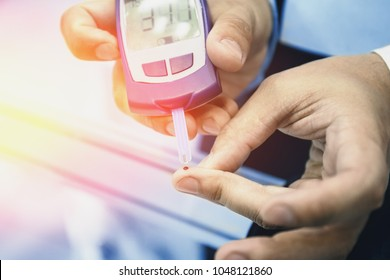 Glucometer - medical device. Man checks blood sugar level test by blood from finger, diabetic disease, insulin protection, toned