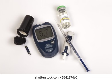 Glucose meter for blood sugar monitor with high blood sugar indication, healthcare medical equipment. Insulin syringe with needle  lying near the meter. Vial with insulin and blood sugar test.