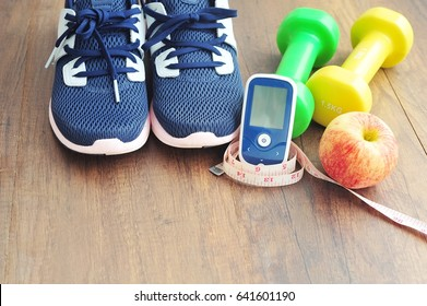 Glucose meter, fruits and dumbbells, running shoe for using in fitness, concept of diabetes.