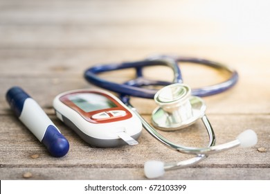 Glucose meter with lancet and stethoscope on wooden table use for Medicine, diabetes, glycemia, health care and people concept.