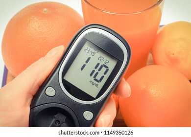 Glucose meter with result of measurement sugar level and fresh natural fruits, concept of diabetes, healthy nutrition and strengthening immunity