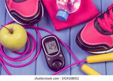 Glukosemesser mit Zuckergehalt, Paar Sportschuhe und Zubehör für Fitness. Diabetes und gesunde sportliche Lebensweisen