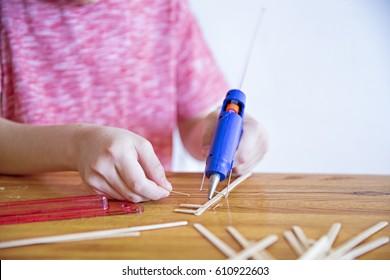 Glue gun in the child's hand. kid glues wooden sticks with a glue gun. closeup