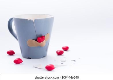 Glued love. A glued broken mug. Gray mug on white background.
