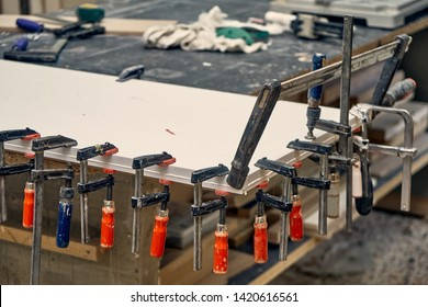 Gluing and clamping table top of acrylic stone in workshop. Furniture manufacture. Close-up