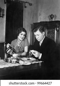 Glum man and adoring woman at breakfast table