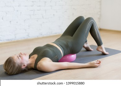 Gluteal bridge on small fit ball, caucasian woman doing pilates with special equipment in fitness studio. Work out, yoga, balance, concentration, healthy spine, sport, smart body and wellness concept.