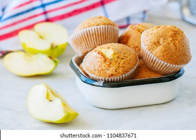 Gluten free almond flour muffins with apples in a bowl on a white stone background.