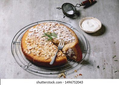 Gluten free almond rosemary homemade cake decorated by almond and sugar powder on cooling rack, serving with sour cream, fork and vintage sieve over grey texture background.