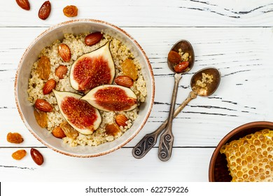 Gluten free amaranth and quinoa porridge breakfast bowl with figs, caramelized almonds, raisins and honey over rustic white table. Top view, overhead, flat lay. Copy space