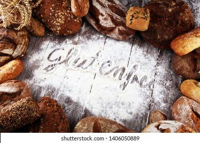 gluten free breads, glutenfree word written and bread rolls on rustic wooden background