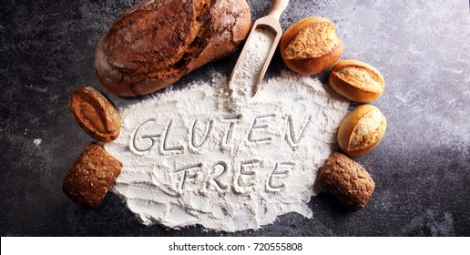 gluten free breads, glutenfree word written and bread rolls on grey background