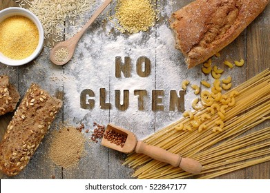 Gluten free flour and cereals millet, quinoa, corn flour polenta, brown buckwheat, basmati rice, bread and pasta with text no gluten in English language with spoon on brown wooden background,up view