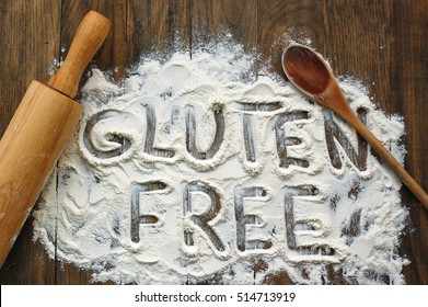 Gluten free flour with text gluten free in English language with wooden spoon and rolling pin on dark brown wooden background,up horizontal view