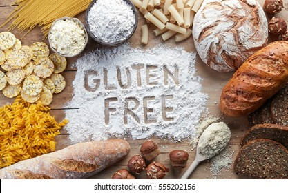 Gluten free food. Various pasta, bread, snacks and flour on wooden background from top view