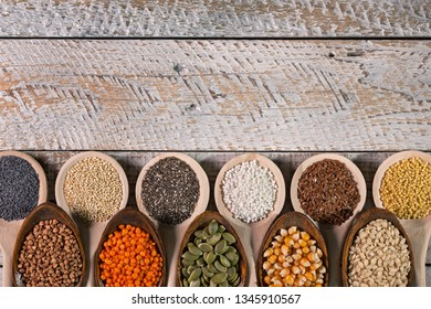 Gluten free grains and seeds variety in wooden spoons - top view, close up. Colorful diverse staple food - harsh lighting