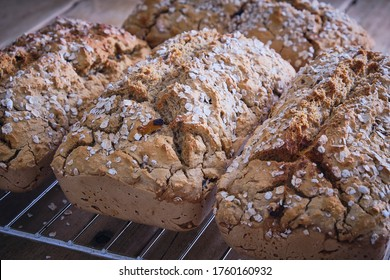 Gluten free rustic brown loaves of bread cooling on a tray
