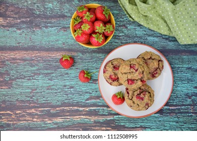 Gluten free strawberry muffins on a plate with fresh organic strawberries
