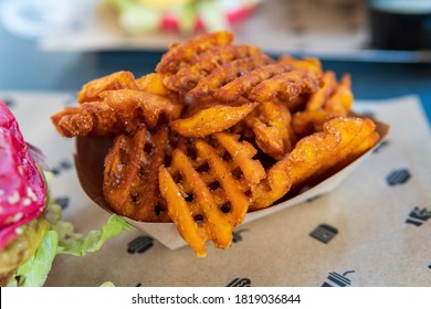 Gluten free sweet potato waffle cut fries served in a vegan restaurant as a side dish for a burger during lunchtime