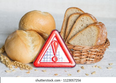 Gluten intolerance with bread wheat and warning sign on white planks