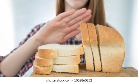 Gluten intolerance concept. Young girl refuses to eat white bread - shallow depth of field - selective focus on bread
