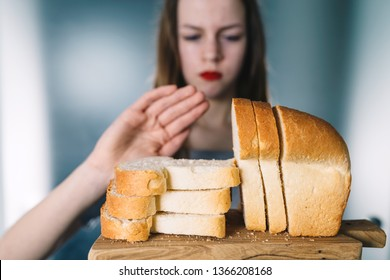 Gluten intolerance and diet concept. Young girl refuses to eat white bread. Shallow depth of field. Selective focus on bread