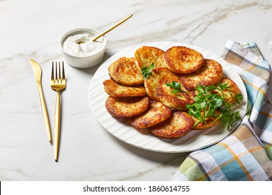 Gluten-free potato pancakes with cottage cheese with garlic, parsley, served with sour cream dip on a plate on a light marble stone background with golden cutlery, top view, close-up