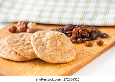 Gluten's cookies with raisins and hazelnuts - three cookies and dried fruit on the background.