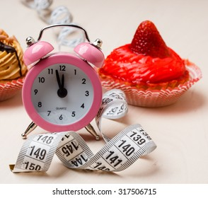 Gluttony and not eat junk sugar foods concept. Time for slimming. Cake cupcakes measuring tape and alarm clock on kitchen table