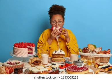 Gluttony and overeating concept. Upset crying ethnic woman eats piece of cake reluctantly, sits at table with many desserts, isolated over blue wall, feels hungry and greedy, wears yellow jacket