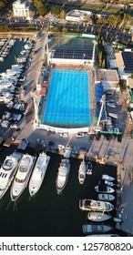 Glyfada, Attica / Greece - December 12 2018: Aerial drone photo of crowded pool built next to busy port with luxury yahcts docked