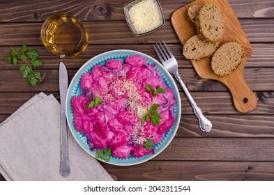 Gnocchi à la sauce à la betterave à la crème, feuilles de blette et tiges sur fond bois. Vue de dessus.