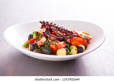 Gnocchi with fresh vegetables, sauce and octopus tentacles. Italian food, gnocchi and octopus with fresh tomato. Fresh pasta with tentacles of octopus. Italian fresh sea food. Mediterranean sea food.