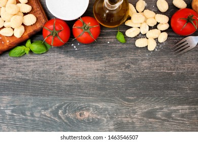 Gnocchi meal ingredients including fresh gnocchi, tomatoes, olive oil, potatoes and basil. Above view, top border against a dark wood background. Copy space.