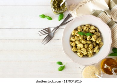 Gnocchi with pesto sauce. Top view table scene over white wood with copy space.