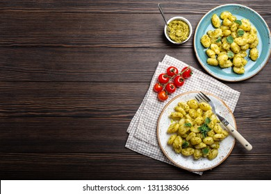 Gnocchi in plates with green pesto sauce, tomatoes and herbs on rustic wooden background with space for text, close up, top view. Traditional dish of Italian cuisine