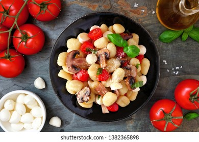 Gnocchi with tomatoes, mozzarella, mushrooms and basil. Above view scene over a dark stone background.