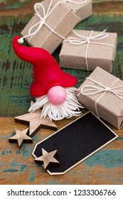 Gnome with gifts and card on a colorful wooden table