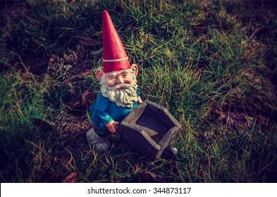 Gnome task - Garden gnome on grass with a wheelbarrow.