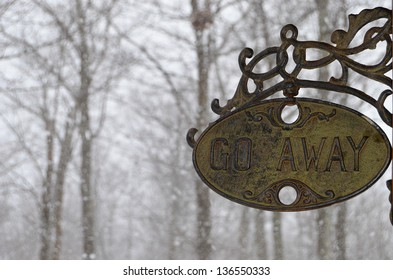 """""""Go Away"""" sign hanging on a porch with a snowy blizzard storming behind it"""