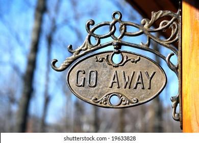 """""""Go Away"""" vintage sign on a log home"""
