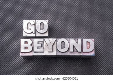 go beyond phrase made from metallic letterpress blocks on black perforated surface