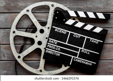 Go to the cinema with film type and clapperboard on wooden background top view