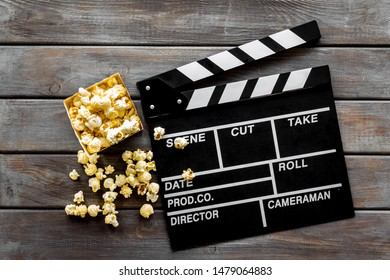 Go to the cinema with popcorn and clapperboard on wooden background top view