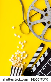 Go to the cinema with popcorn, film type and clapperboard on yellow background top view